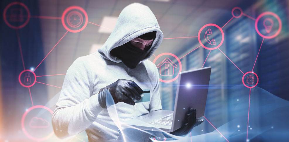 Man wearing a white hooded sweatshirt and a mask holding a credit card and laptop
