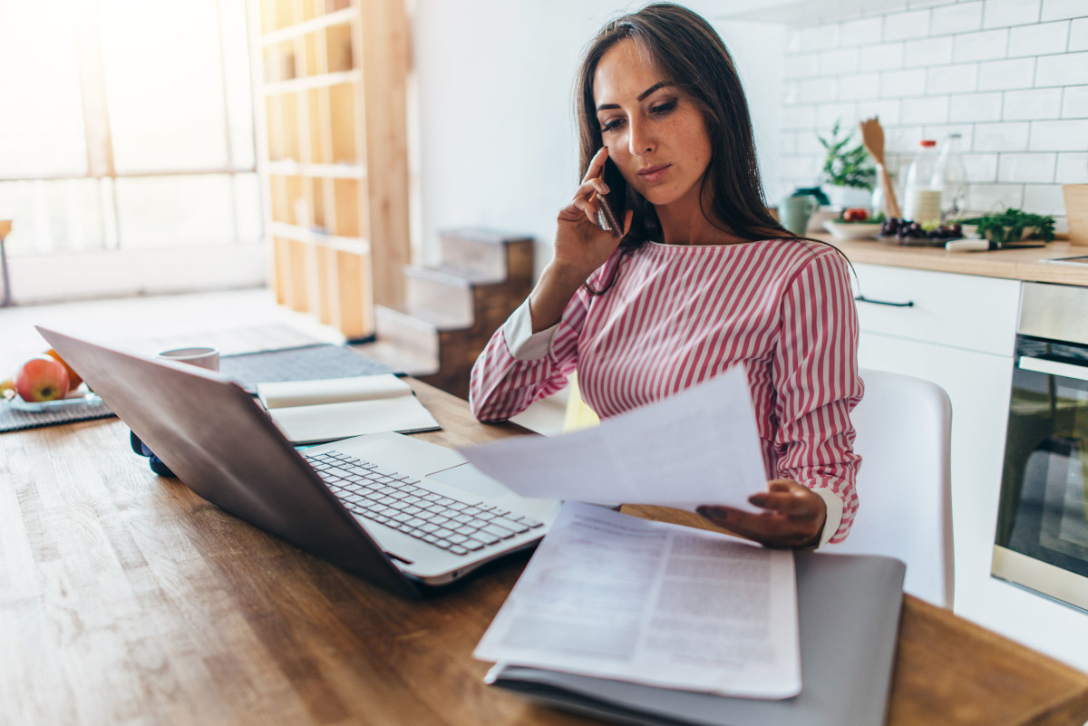 Woman on Phone, Using Laptop, and Looking Over Papers in Home Office