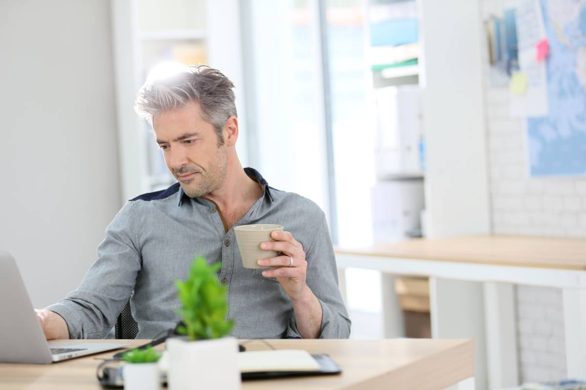 A man working from home using a laptop and drinking coffee