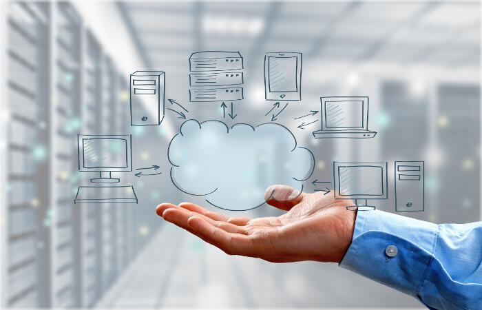 Businessman's Hand Holding Illustration of Cloud Computing Concept in Room with Server Racks on Light Background
