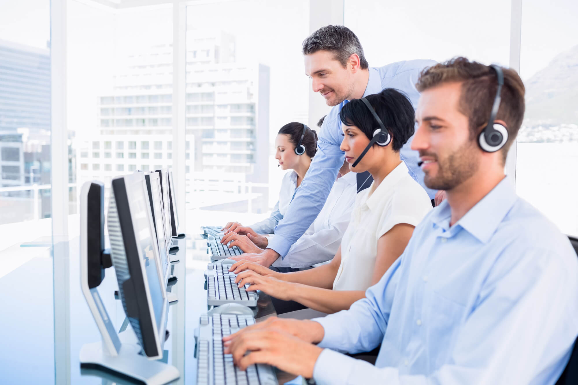 Customer Service Reps on Computers while Man with Salt and Pepper Hair Overlooks Them