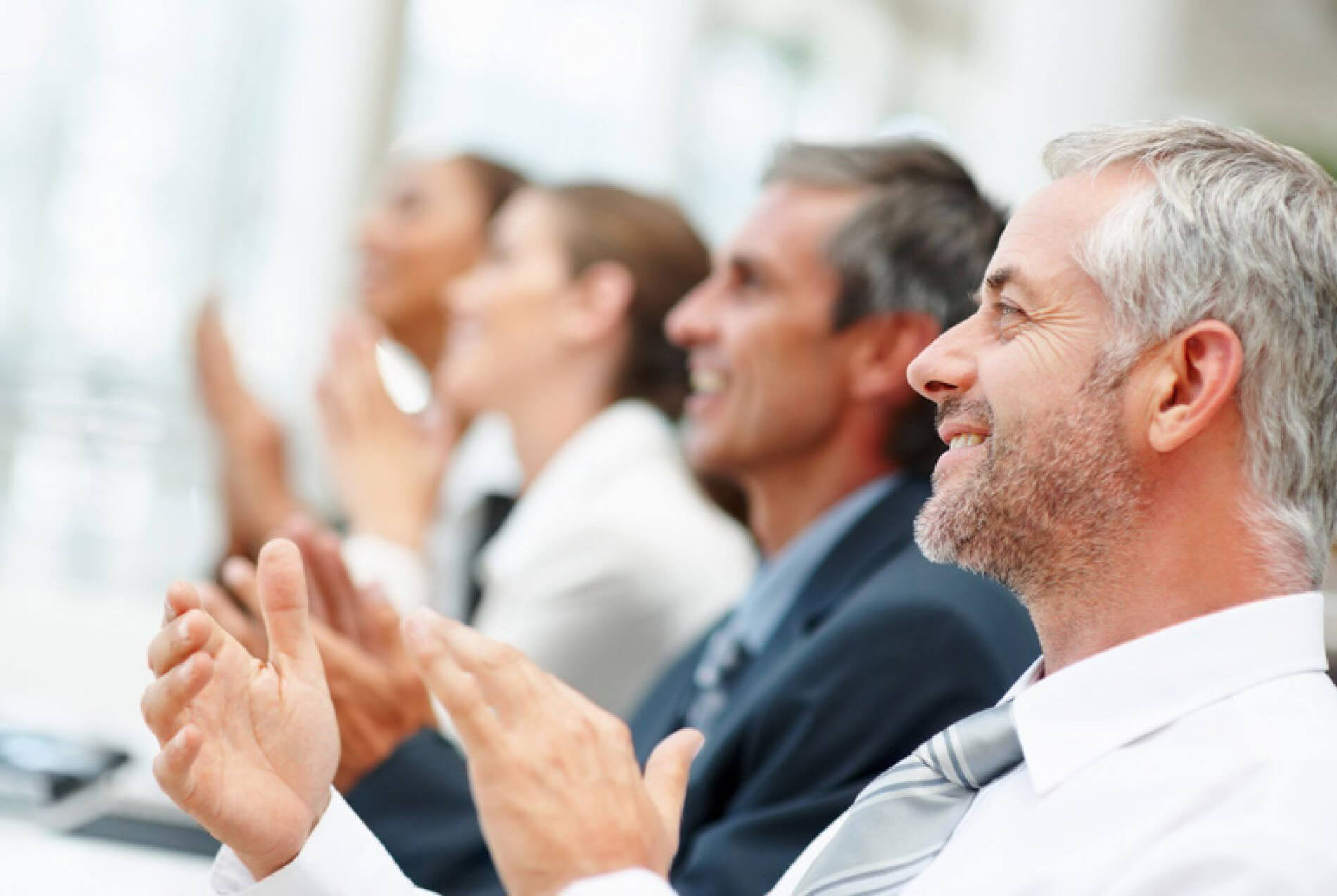 Close Up of Mature Businessman with Additional People Blurred in Background Clapping