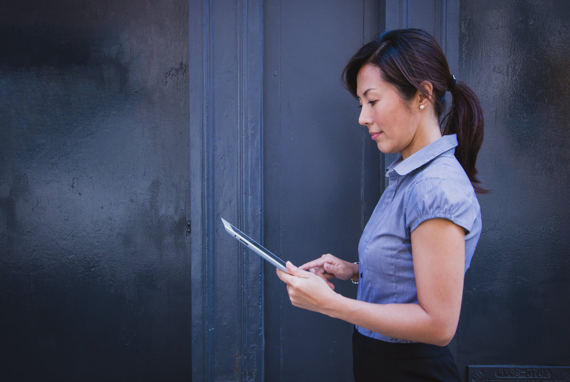Woman in Blue Blouse Holding Tablet with Distressed Dark Wall in Background